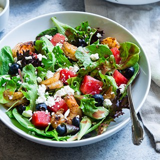 salad with greens, tomatoes, and feta cheese in a white bowl