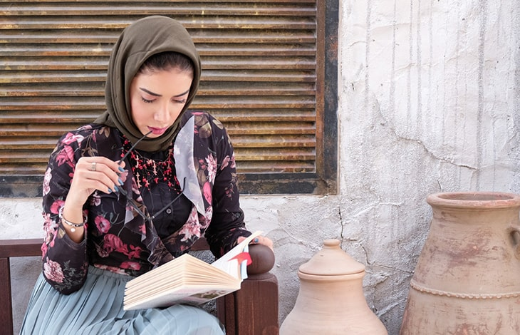 a person wearing a black and pink floral shirt and a brown headscarf sitting on a bench reading a book