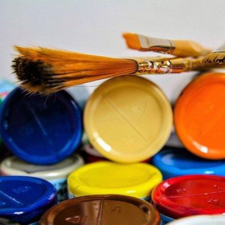 blue, yellow, orange, red, and brown craft paint in bottles with paintbrushes on top