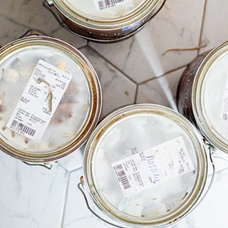 paint cans on white tile with labels on the lids