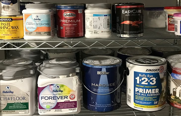 various cans and tubs of paint on metal shelving