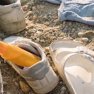 a sneaker with an orange sunscreen bottle in it sits on sand next to a white sandal and light blue towel