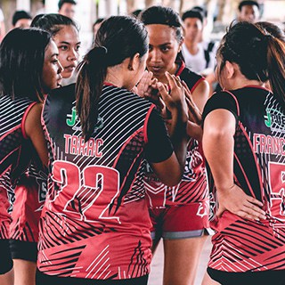 huddled volleyball team in red and black jerseys