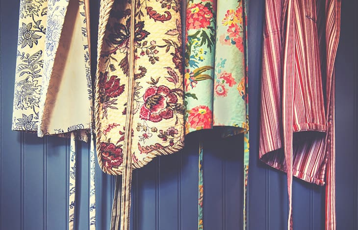 hanging floral and striped aprons hanging against a blue wall
