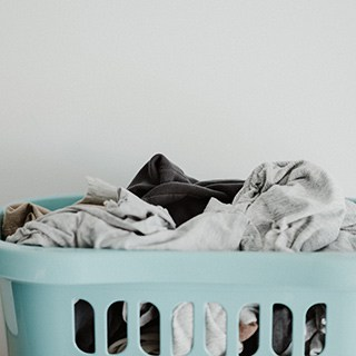 mint blue laundry basket filled with gray and black clothes