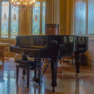 a black grand piano in a room with stained glass windows and a chandelier