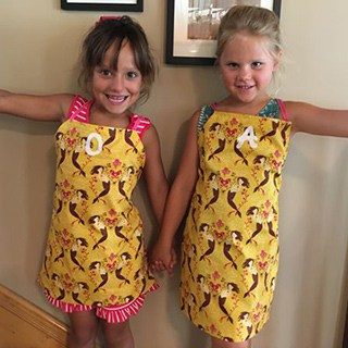 two girls wearing matching yellow mermaid aprons