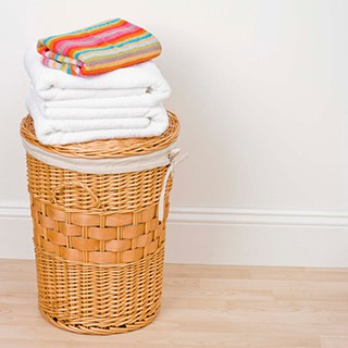 folded towels stacked on top of a tall wicker laundry basket