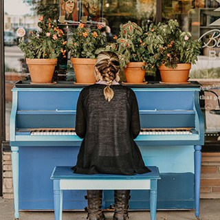 A person in black plays a blue piano with flowerpots on top