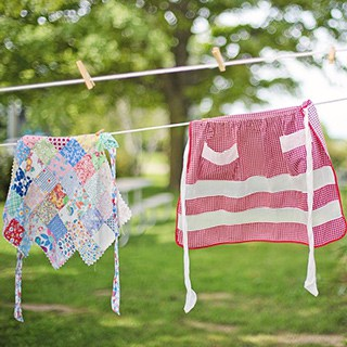 quilted and striped aprons hanging on a clothesline