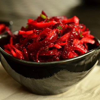 red shredded beetroot in a black bowl