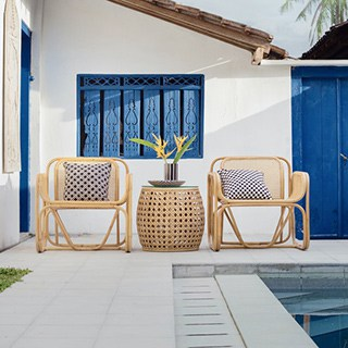 Two light wood chairs beside a pool and pool house
