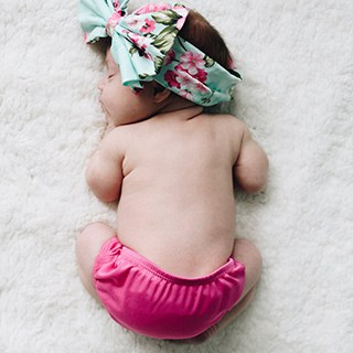 Newborn baby wearing a mint blue and pink hair bow and bright pink diaper cover