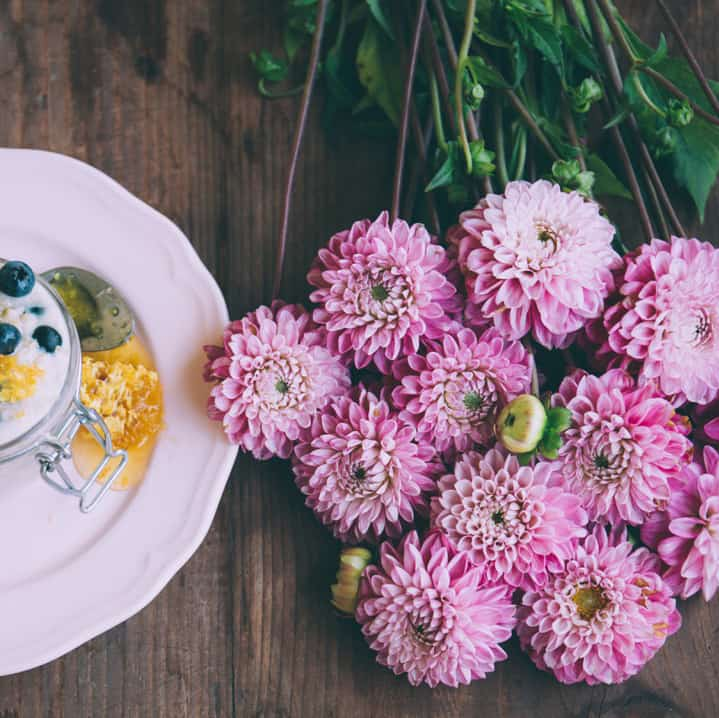 cut pink chrysanthemums on a wood table beside a plate