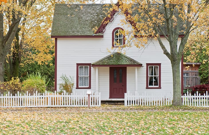 small white cottage house with gray and burgundy trim and a white picket fence
