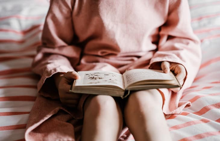 A person in an oversize coral sweater holding an open book in their lap