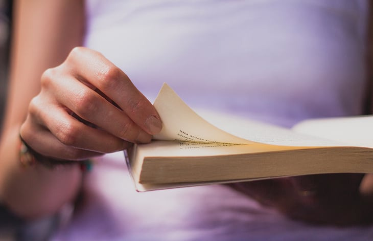A person in a white shirt, turning the page of a book