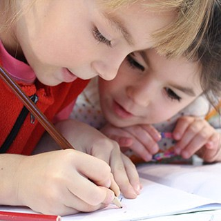 Two children writing in a notebook together