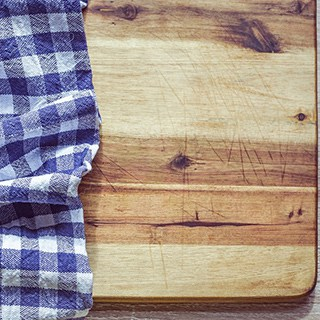 a natural wood cutting board partially covered by a blue and white checked dishcloth