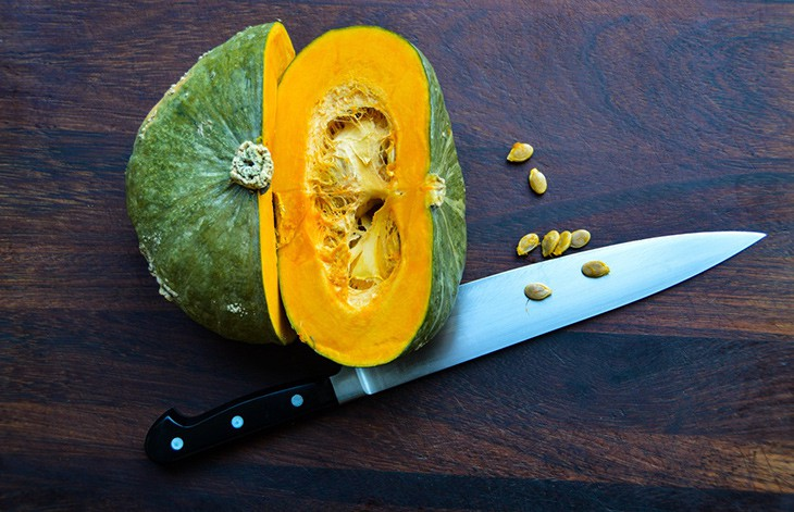 Halved squash and chef's knife on dark wood