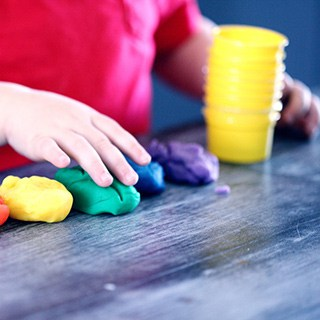 A child in a red shirt lines up colored clay or playdough on a table