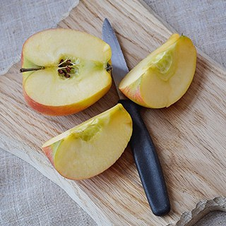 a cut apple and paring knife on a wood cutting board