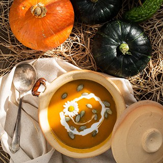 a bowl of soup next to black and orange winter squash