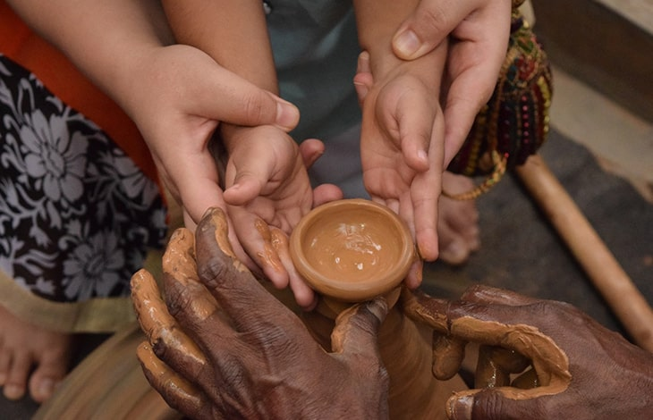 adults guide a child's hands throwing pottery