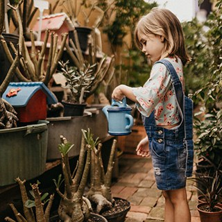 a child watering potted plants outside