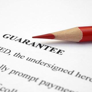 """A red pencil tip beside the word """"guarantee"""" on a written document"""