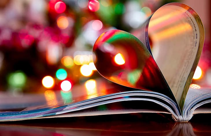 an open book's inner pages rolled to make a heart on a background of blurred holiday lights