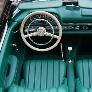 aerial view of a convertible vehicle with a silver wheel and teal interior