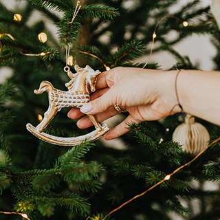 a person hangs a rocking horse ornament on a Christmas tree