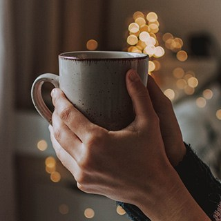 a mug grasped in a person's hands with Christmas lights in the background