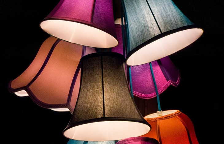 Bell-shaped, lit lampshades in various colors hang gathered together on a black background