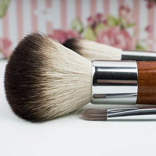 makeup brushes lying on a white surface with pink striped and floral wallpaper in the background
