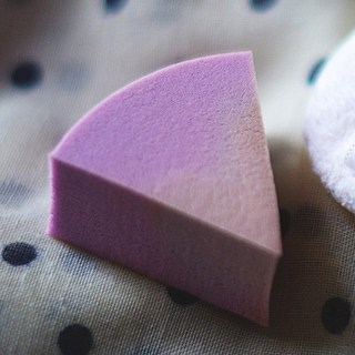 a wedge-shaped makeup sponge with purple product on it on a white cloth with black dots