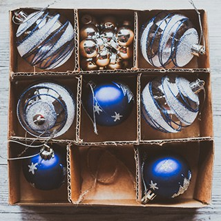 blue and white glass holiday ornaments stored in a sectioned cardboard box