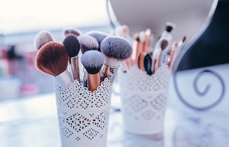 white lacy cups holding makeup brushes of various sizes