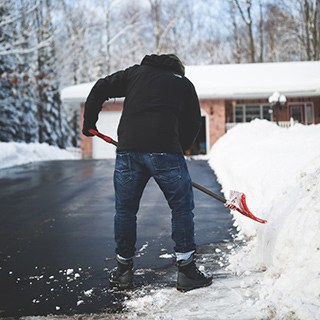 a person wearing jeans and a black hoodie shoveling snow
