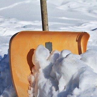 yellow snow shovel with a wood handle