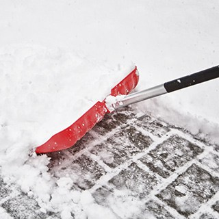 red shovel with silver and black handle, pushing snow from a brick walk