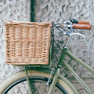 a wicker bike basket on the front of a green bicycle in front of a stone wall