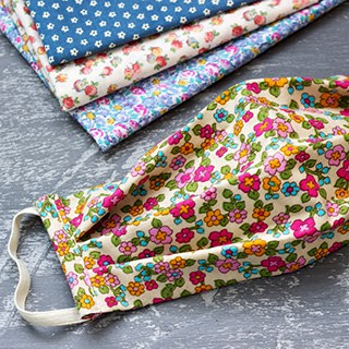 a floral facemask open on a table next to floral and polka-dotted quilters cotton