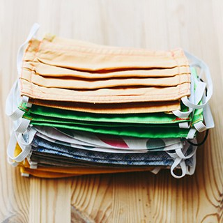 a stack of clean fabric face masks in various colors