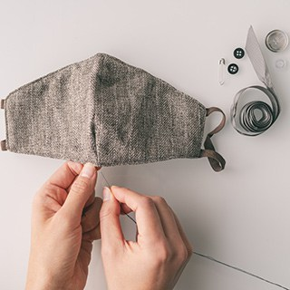 hands sewing a gray face mask above a white table