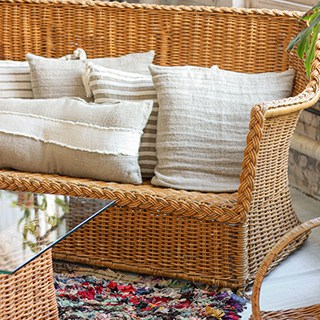 A wicker loveseat with white pillows on it beside a wicker chair and table
