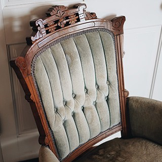 the back of a used chair with wood frame and tufted upholstery.