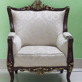 antique upholstered chair with carved frame and white cushions