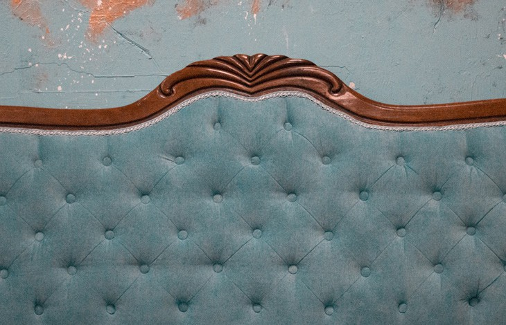 Teal tufted headboard with cherry wood trim